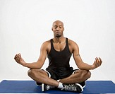 Man in sportswear doing yoga, studio shot