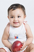 Close-up of a baby girl smiling and holding an apple