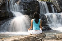 Thailand, Chiang Mai, Sukantara Resort, young woman meditating in front of waterfall, rear view