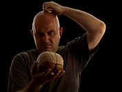 Bald man holding model of brain and scratching head