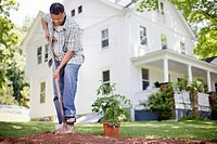 Mature man digging with spade in house backyard