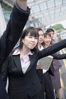 Business executives hailing a taxi at an airport