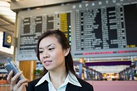 Close-up of a businesswoman at an airport holding a mobile phone