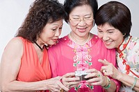 Close-up of three senior women looking at a digital camera and smiling