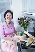 Portrait of a senior woman holding dumplings in a bamboo steamer