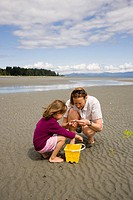Young mother with 5-year old daughter, collect shells on beach at low tide, Parksville, British Columbia, Canada