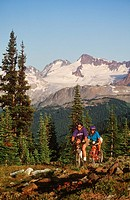 young couple ride bikes in alpine area, Whistler, British Columbia, Canada