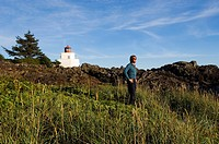 Man on Wild Pacific trail at Ucluelet, Amphritite Point lighthouse, Vancouver Island, British Columbia, Canada