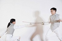 Male and a female fencer fencing