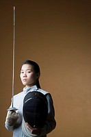 Portrait of a female fencer holding a sword and a fencing mask