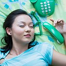 Close-up of a young woman sleeping with a telephone beside her