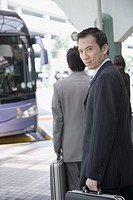 Portrait of a businessman holding a suitcase and walking