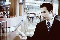 Close-up of a businessman holding a pocket diary at an airport