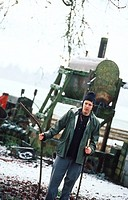 Man Standing in Front of Farm Equipment in Winter