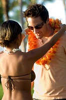 Woman putting lei on Tourist, Maui, Hawaii