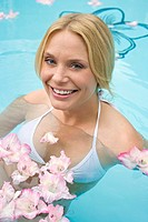 Germany, young woman in pool with flowers
