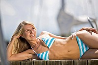 Young woman wearing bikini lying on jetty, close-up