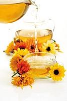 Calendula tea being poured into tea cup, close-up