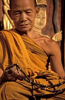 Old Buddhist Monk holding Beads