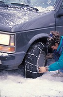Woman Putting Chains on a Tire
