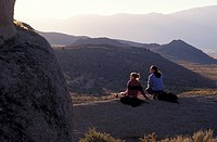 Man and Woman Sitting on Rock Together