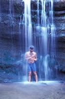 Man Standing Under a Waterfall