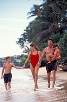 Family Walking Along Beach And Smiling