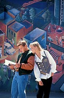 Young Couple Standing In Front Of Mural