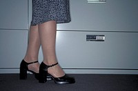 Caucasian Woman Standing Next To A Filing Cabinet