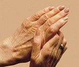 Senior woman rubbing hands in apparent pain