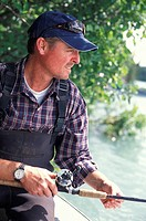 Fisherman in Cap and Waders Holding Rod