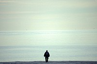 Man Walking Along An Empty Beach