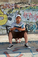 Portrait of a young man sitting on a soccer ball and holding a book