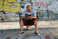 Young man sitting on a soccer ball and reading a book