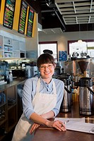 Portrait of a female store clerk standing in a coffee shop and smiling