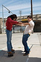 Side profile of a young man helping a young woman in skateboarding