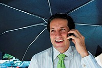 Businessman talking on a mobile phone and smiling under an umbrella