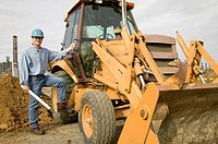 Man Standing Next to Bucket Loader