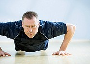 Mature man doing push-ups, portrait
