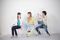 Young women sitting on chairs