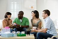 Four young people sitting in living room at home with coffee, exchanging presents