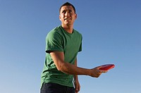 Man about to throw flying disc, standing against clear sky, upper half