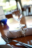 Table napkin with glass on table, close-up