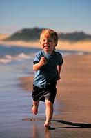 Boy 3-4 running on beach, smiling, portrait