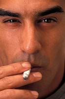 Young man smoking cigarette, close-up