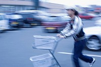 Young Man Pushing an Empty Shopping Cart