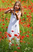 Girl 8-9 playing violin in flower field