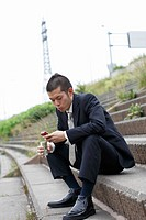 Businessman Holding and Dialing a Cell Phone
