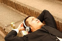 Businessman Lying on Steps and Listening to Music