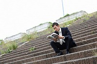 Businessman Outdoors on Steps Reading a Comic Book